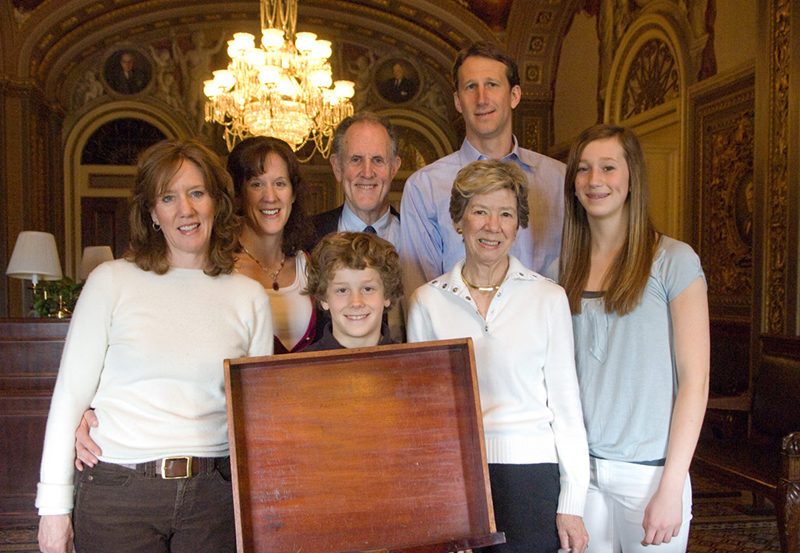 Photograph of Senator Ted Kaufman, his wife Lynne, and their family posing with the desk drawer to his Senate desk, 2009 April 7